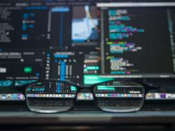 Image of code on a computer with glasses in front